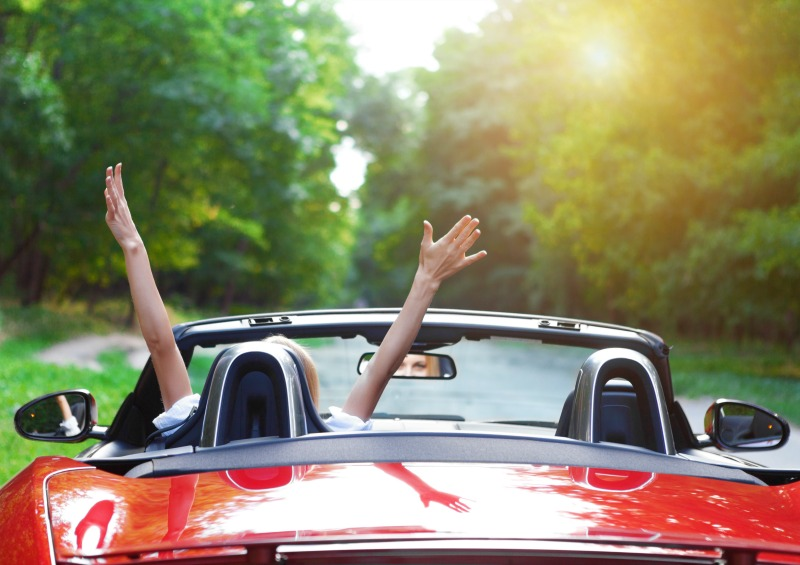 Happy beautiful blond young woman driving a sports car